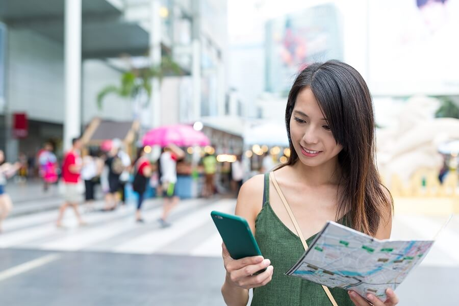 woman in the city checking her location through phone apps and map