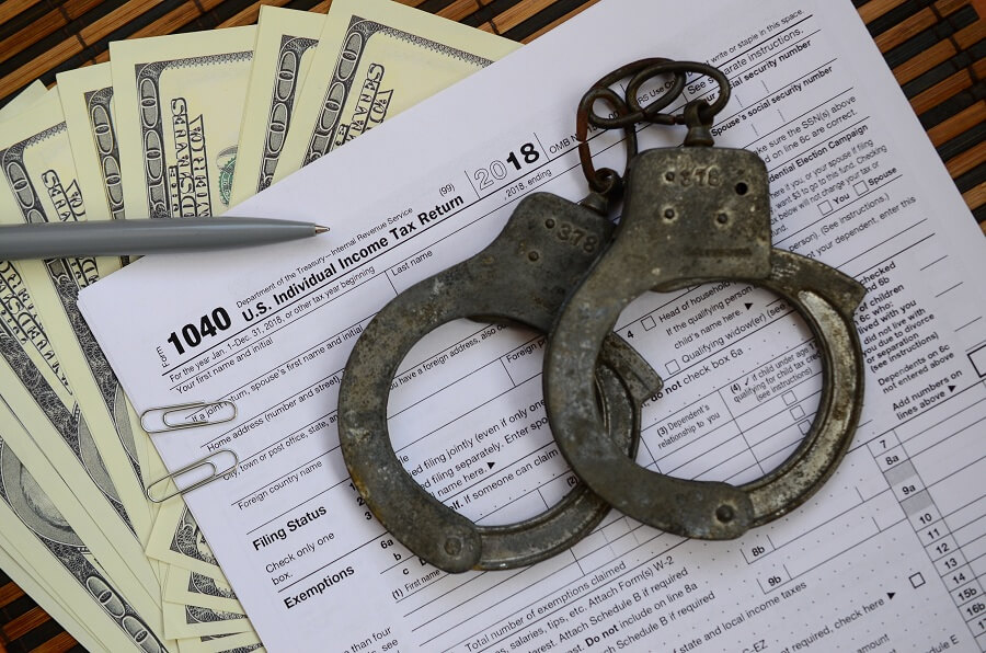 police handcuffs on tax form and money